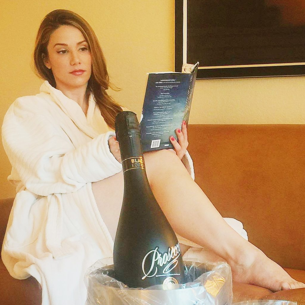 Girl Reading a book and drinking champagne